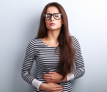 Beautiful stressed business woman in eyeglasses suffering from pain in stomach