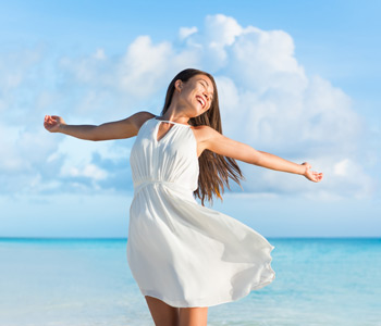 Freedom young woman with arms up outstretched to the sky with blue ocean