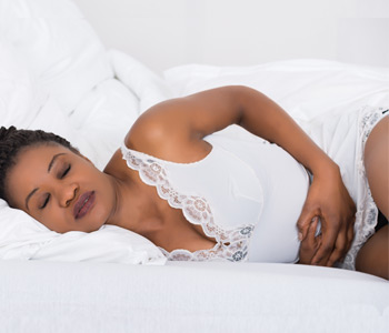 Young African Woman Suffering From Stomach Ache Lying On Bed
