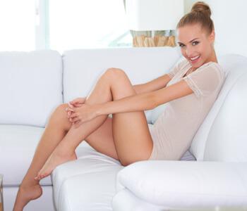 Beautiful introspective woman on white sofa